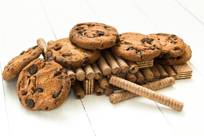 A montanha misturou rolos do waffle do chocolate, cookies e o waffle clássico em uma tabela branca de madeira Doce-toothers imagem de stock royalty free