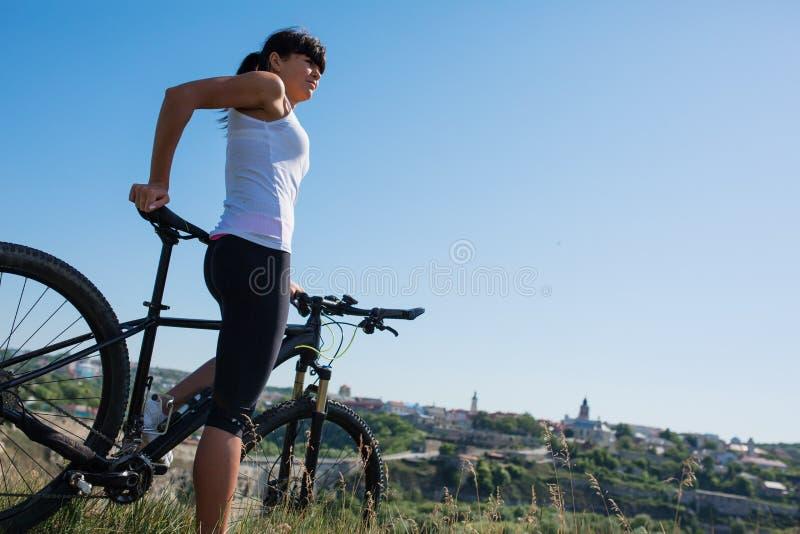 A montanha que biking a menina desportivo feliz relaxa no campo ensolarado dos prados foto de stock royalty free