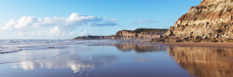 A montanha refletiu na água lisa da praia Areia Branca Lourinha, Portugal, fotos de stock