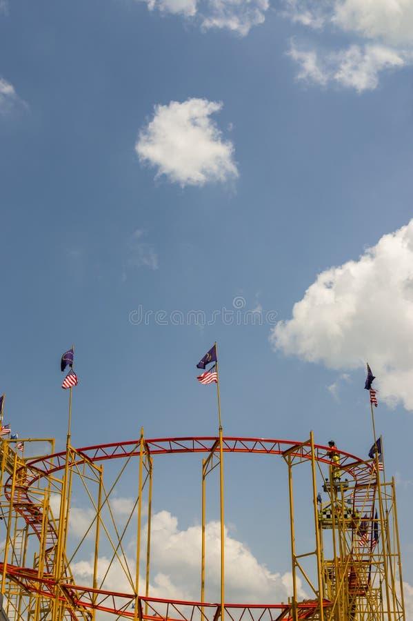 Montanha russa com a bandeira de ondulação fotografada para cima contra o céu brilhante e azul com sol e as nuvens brancas pequen imagens de stock royalty free