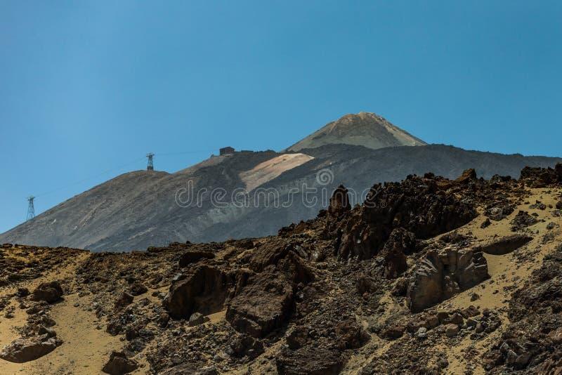 Montanha Teide com poucos pontos brancos da neve, sob o céu azul brilhante Cabo aéreo no parque nacional de Teide da inclinação e fotografia de stock