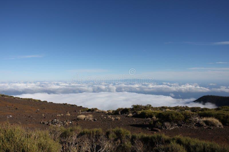 Montanhas acima das nuvens e do céu azul fotos de stock royalty free