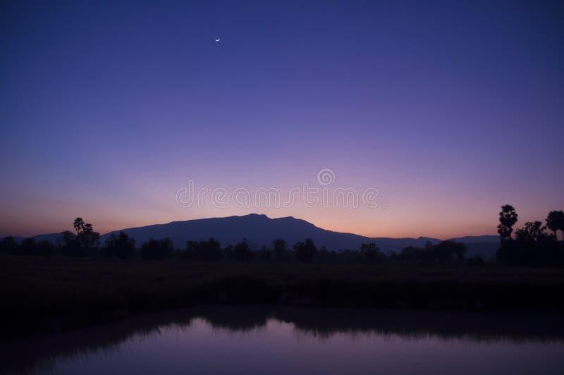 Montanhas azuis do crepúsculo refletidas no lago fotografia de stock royalty free