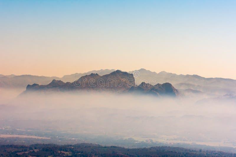 Montanhas bonitas da floresta da natureza da paisagem e vale da cidade pequena na névoa imagem de stock