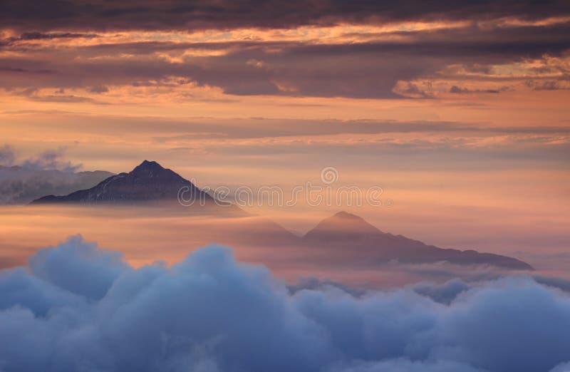 Montanhas cônicas na névoa do outono e no céu vermelho na manhã fotos de stock