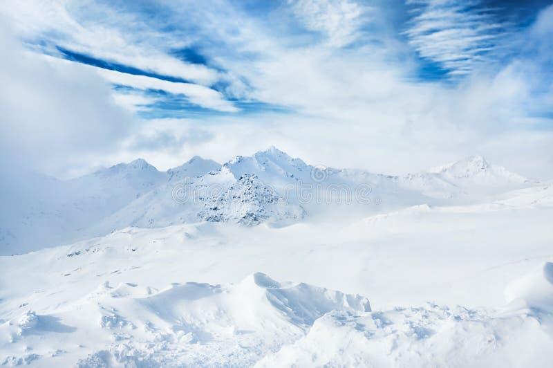 Montanhas cobertos de neve do inverno e céu azul com nuvens brancas fotografia de stock royalty free