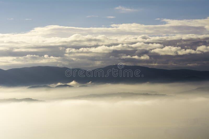 Montanhas como ilhas em um oceano das nuvens e da névoa imagens de stock royalty free