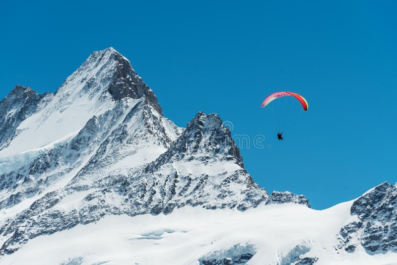 Montanhas dos cumes completas da neve com céu azul e do parapente no ar no verão em Suíça imagem de stock