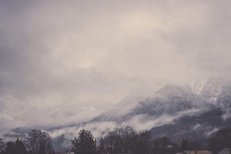 Montanhas dos cumes de Bernese cobertas na névoa sob o céu cinzento imagens de stock