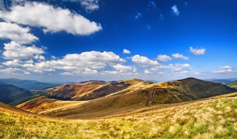 Montanhas e campo da grama fresca verde sob o céu azul fotografia de stock royalty free