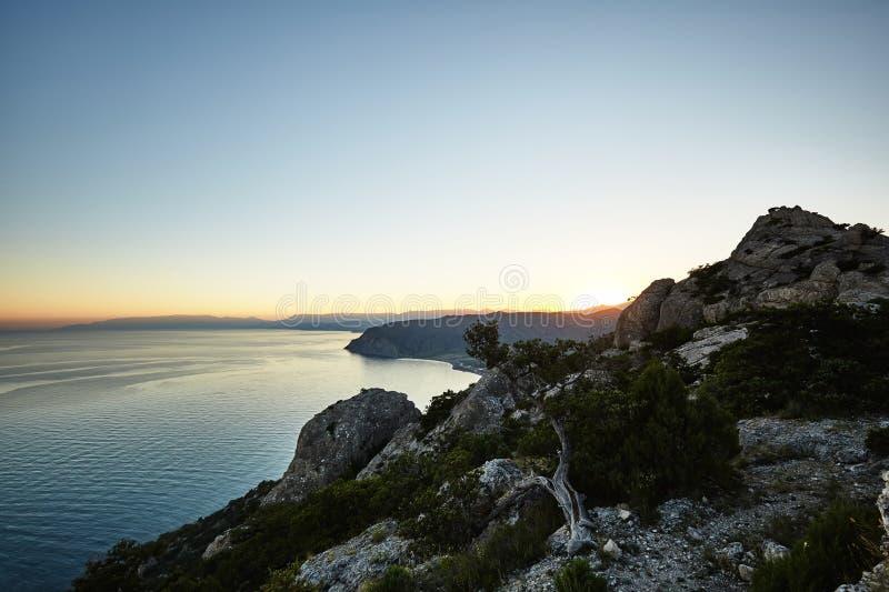 Montanhas e mar no por do sol fotos de stock