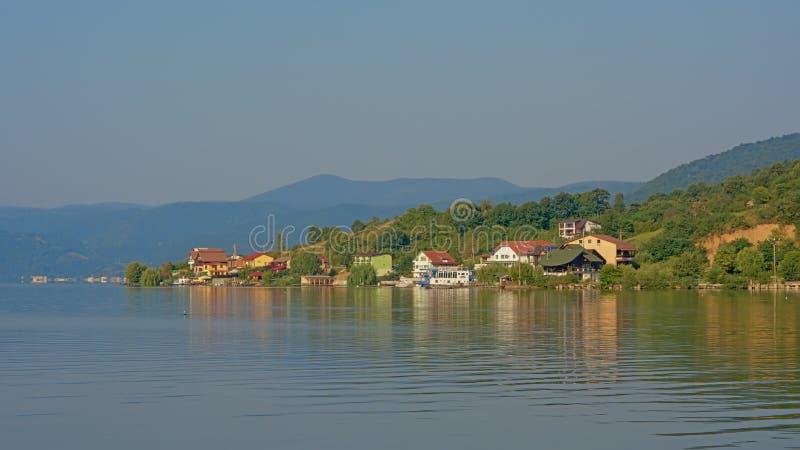 Montanhas e vila nas terraplenagens do rio Danúbio, Romênia na luz do amanhecer imagem de stock