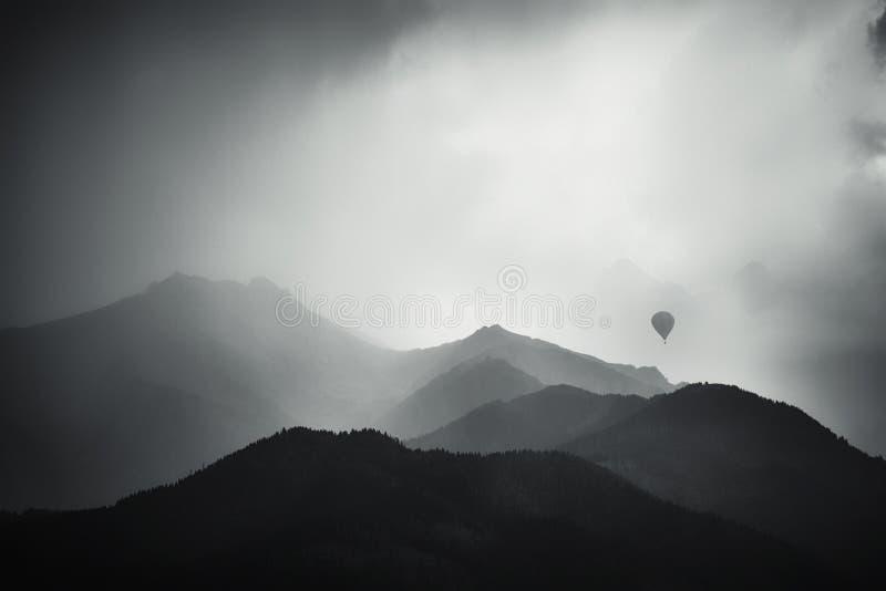 Montanhas enevoadas e balão de ar quente fotografia de stock royalty free