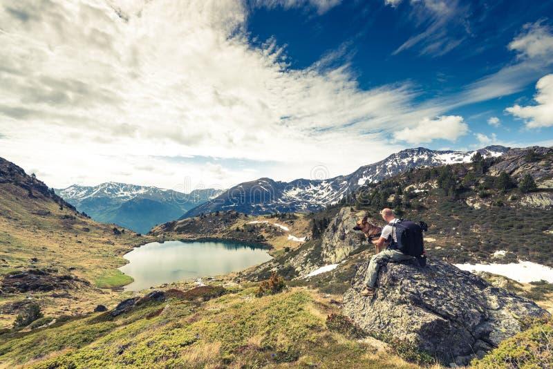 Montanhas, hikker e cão de Adorra imagens de stock