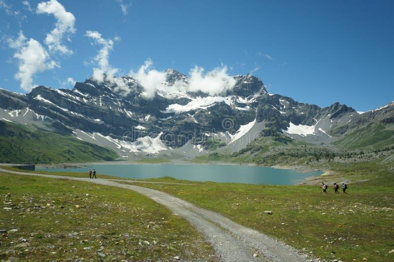 Montanhas, lago e céu azul em Suíça imagem de stock royalty free