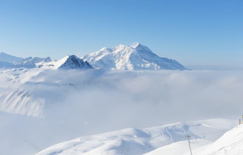 Montanhas nas nuvens com neve no inverno foto de stock
