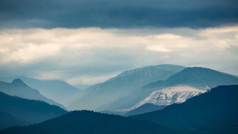 Montanhas nas nuvens na costa do Lago Baikal fotografia de stock royalty free