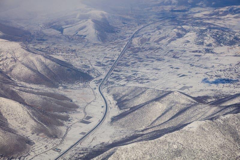 Montanhas nevado fundo, estrada entre eles Foto aérea da janela do ` s do avião foto de stock