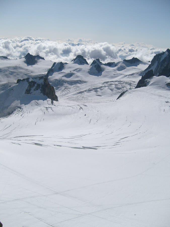 Montanhas nevado nas nuvens imagens de stock