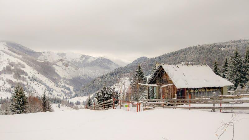 Montanhas nevados e uma casa de campo na parte superior imagens de stock royalty free