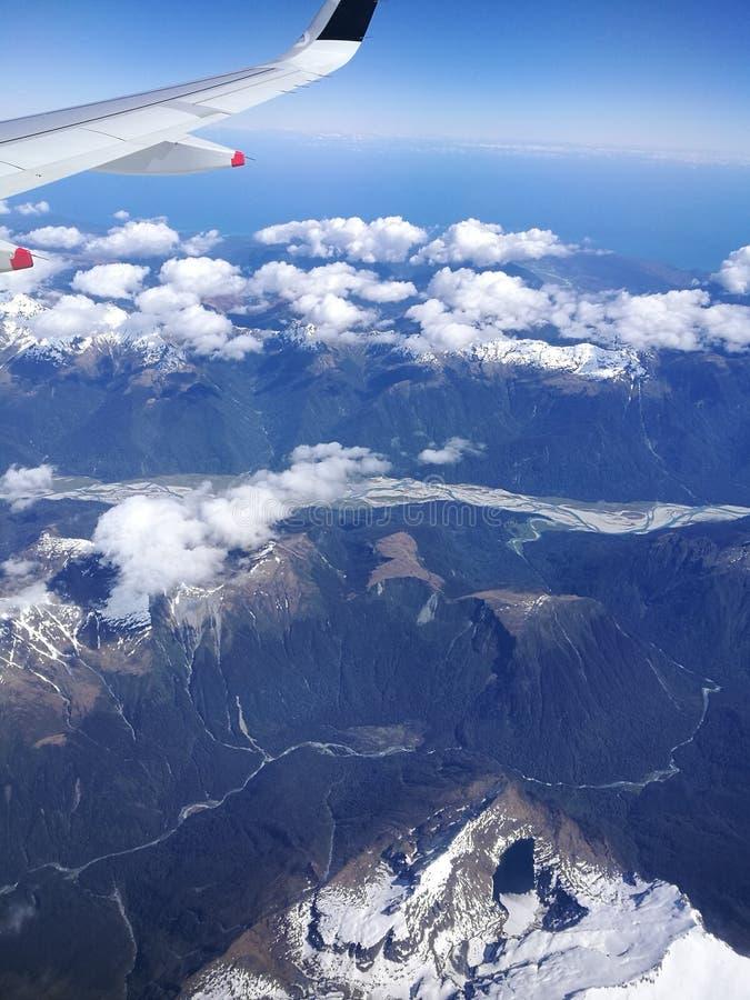 montanhas Neve-tampadas do céu, azul imagens de stock