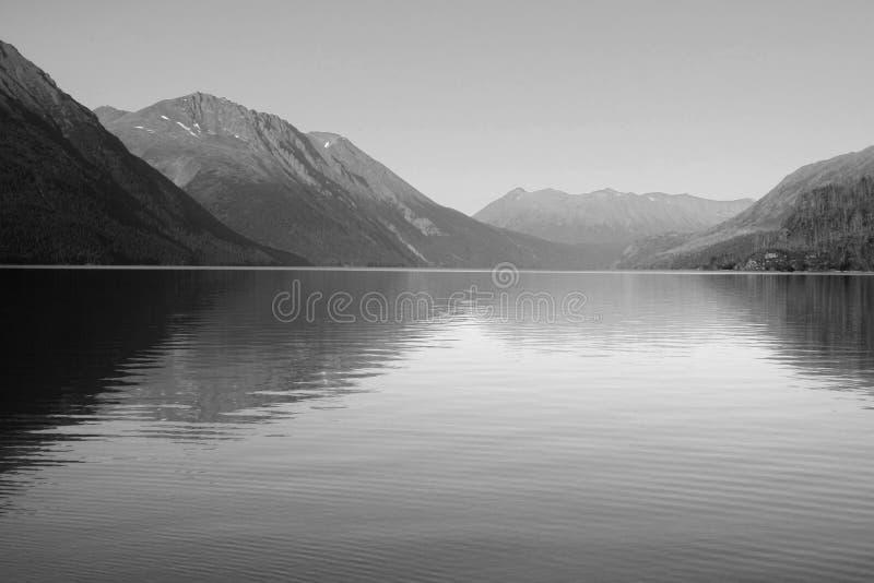 Montanhas refletidas monocromáticas no lago Kenai imagens de stock