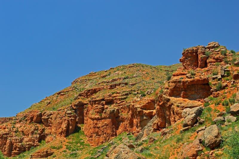 Montanhas rochosas vermelhas perto da cidade de Tamasha imagens de stock royalty free