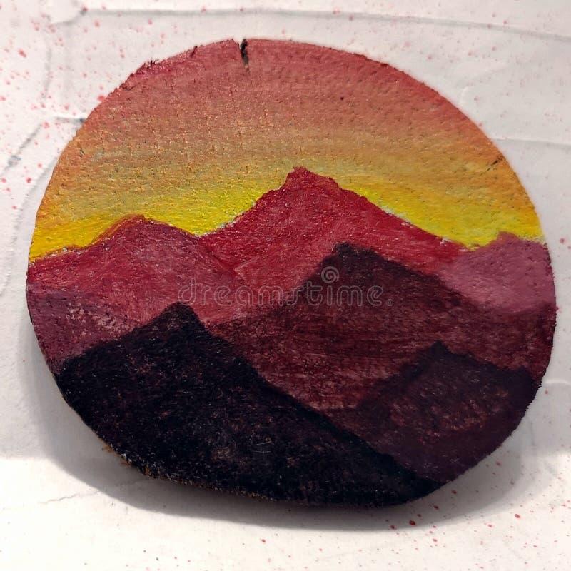 Montanhas sob o por do sol/luz do nascer do sol - pintados em uma fatia de madeira imagem de stock