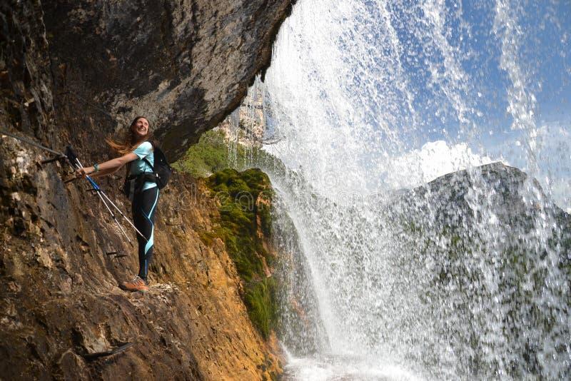 Montanhista da mulher no penhasco pela cachoeira fotografia de stock