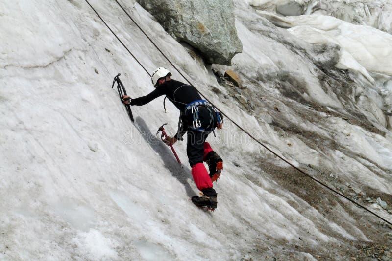 Montanhista de gelo com climbe dos machados de gelo a parede fotos de stock