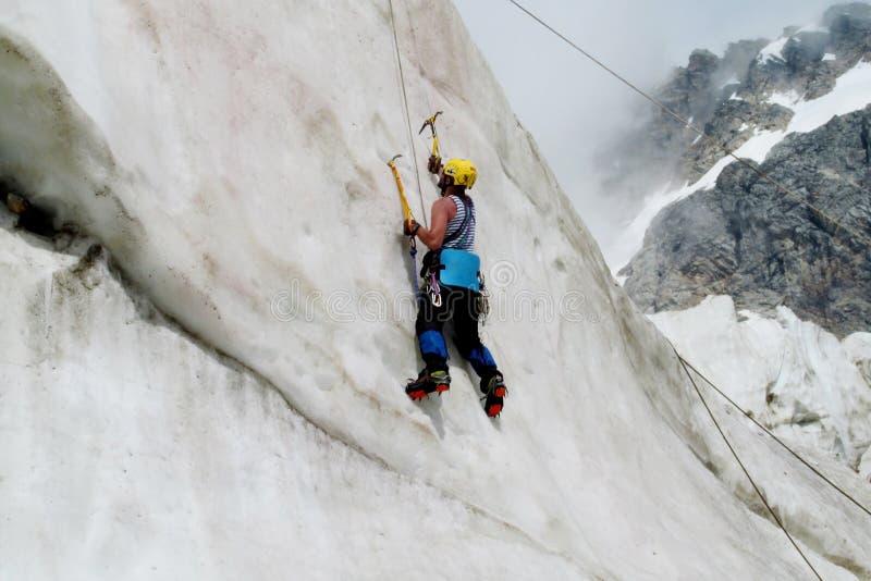 Montanhista de gelo com escalada vertical dos machados de gelo imagem de stock
