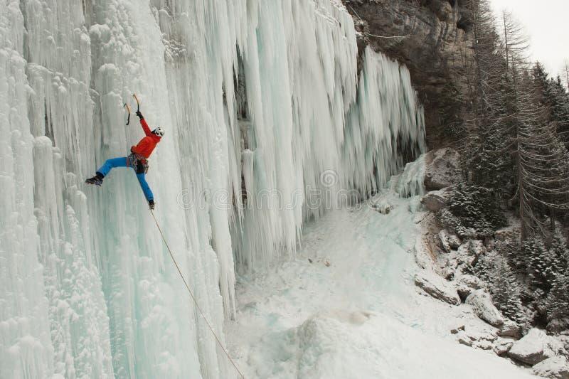Montanhista de gelo em uma cachoeira congelada imagens de stock royalty free