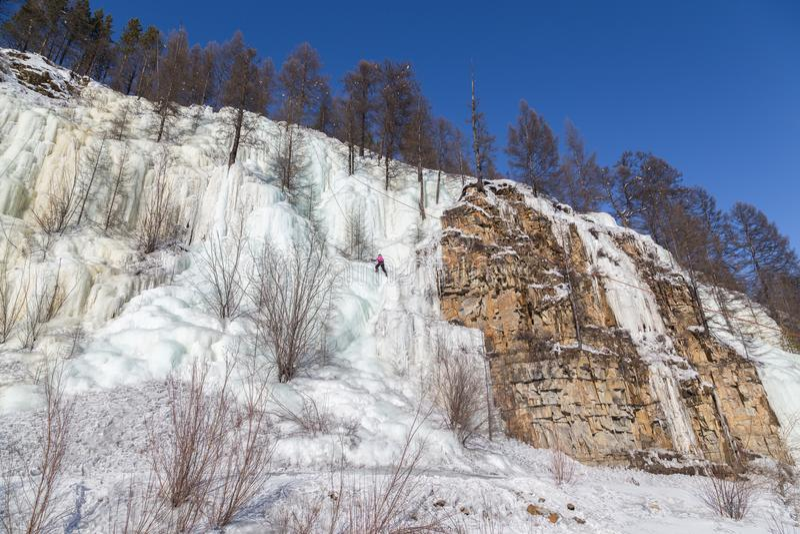 Montanhista de gelo em uma cachoeira congelada plano total imagem de stock royalty free