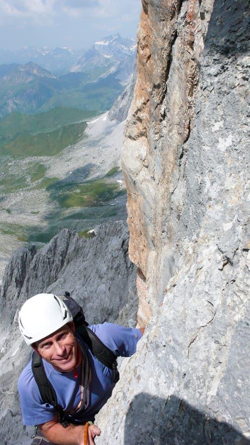 Montanhista de montanha masculino em uma rota íngreme da escalada nos cumes suíços perto de Klosters fotos de stock royalty free