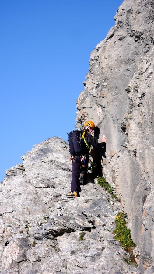 Montanhista de montanha masculino no início de uma rota de escalada longa sob um céu azul claro foto de stock