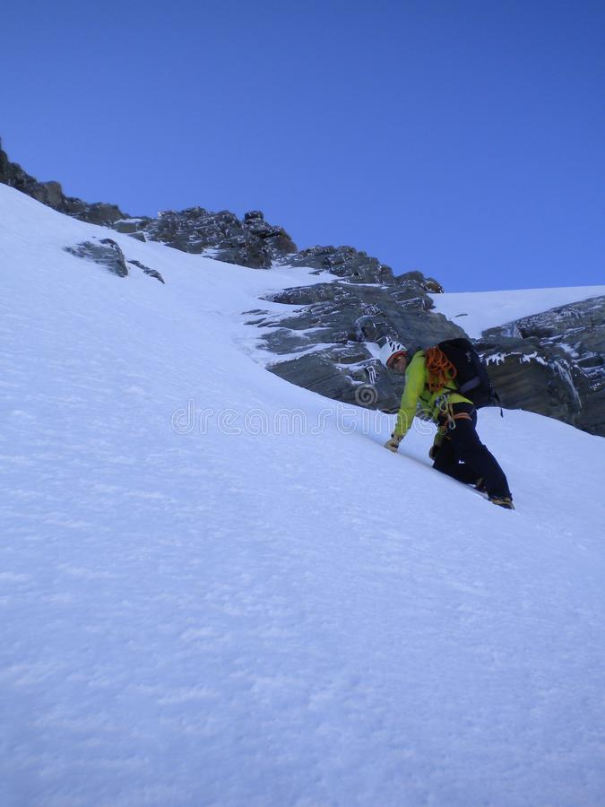 Montanhista de montanha masculino que dirige acima de uma sarjeta e de um couloir íngremes da neve cedo na manhã em sua maneira a fotografia de stock