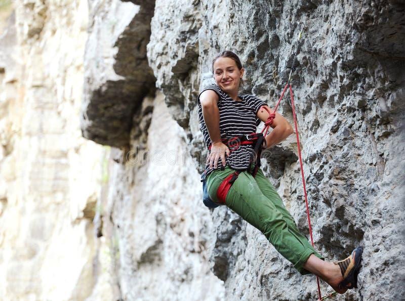 Montanhista de rocha da menina que descansa ao escalar no penhasco fotografia de stock royalty free