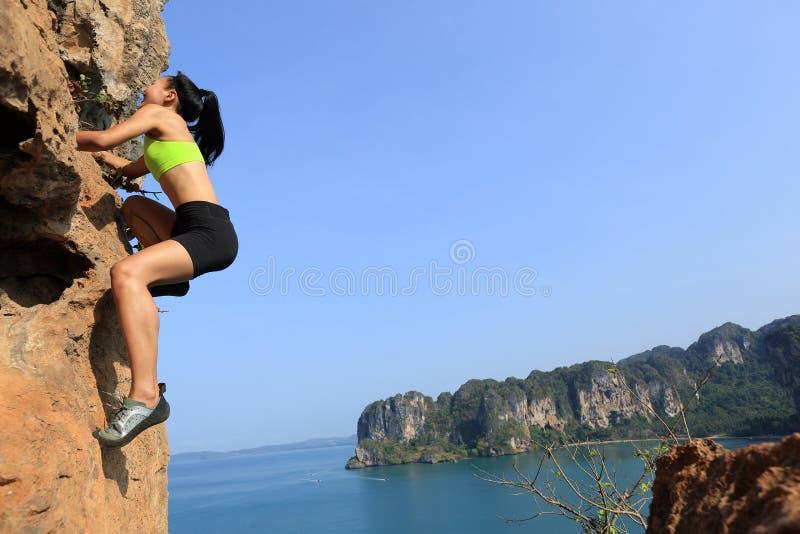 Montanhista de rocha da mulher que escala na rocha da montanha do beira-mar fotos de stock royalty free