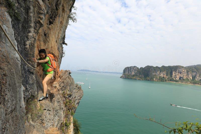 Montanhista de rocha da mulher que escala no penhasco da montanha do beira-mar imagem de stock royalty free