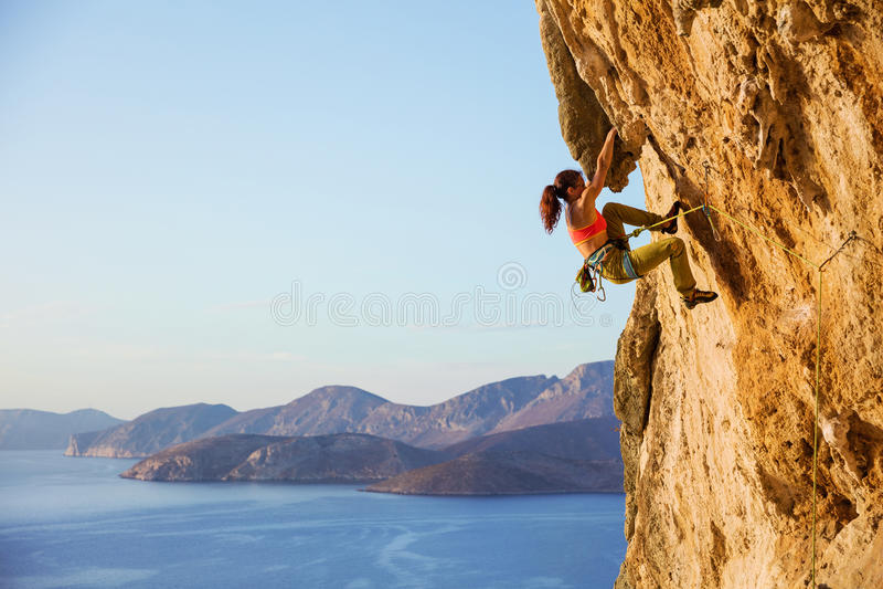 Montanhista de rocha fêmea na rota desafiante no penhasco, vista da costa fotografia de stock