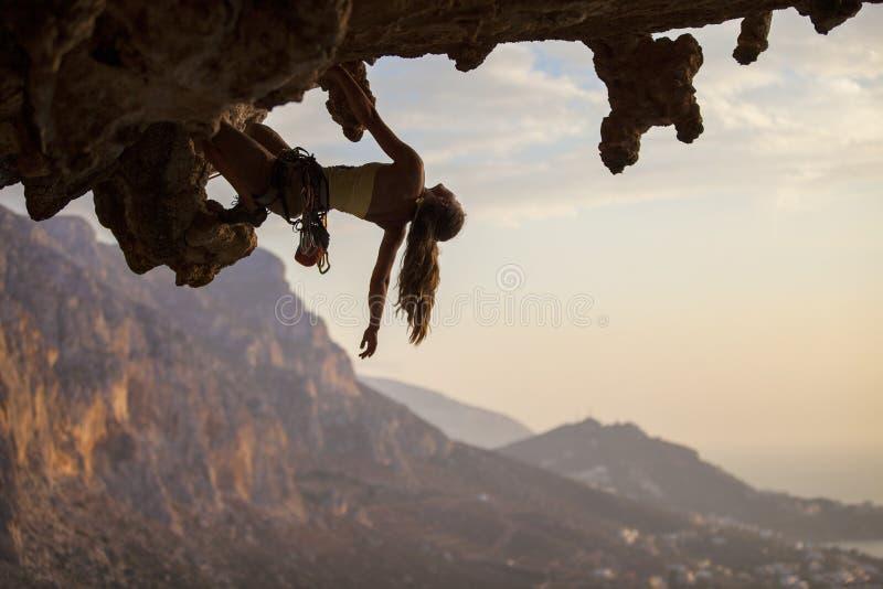 Montanhista de rocha fêmea no por do sol imagem de stock