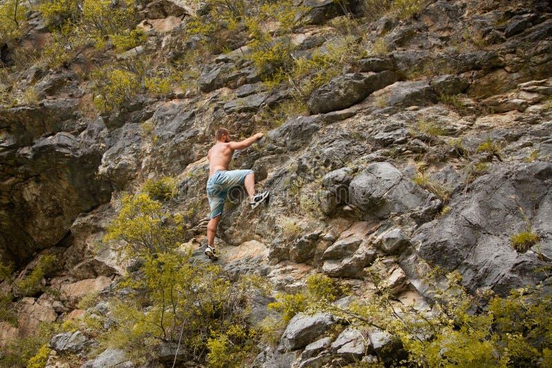 Montanhista de rocha que adere-se a um penhasco fotos de stock royalty free