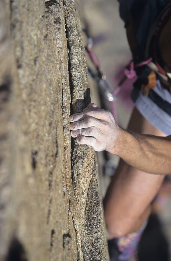 Montanhista de rocha que aferra-se ao penhasco foto de stock