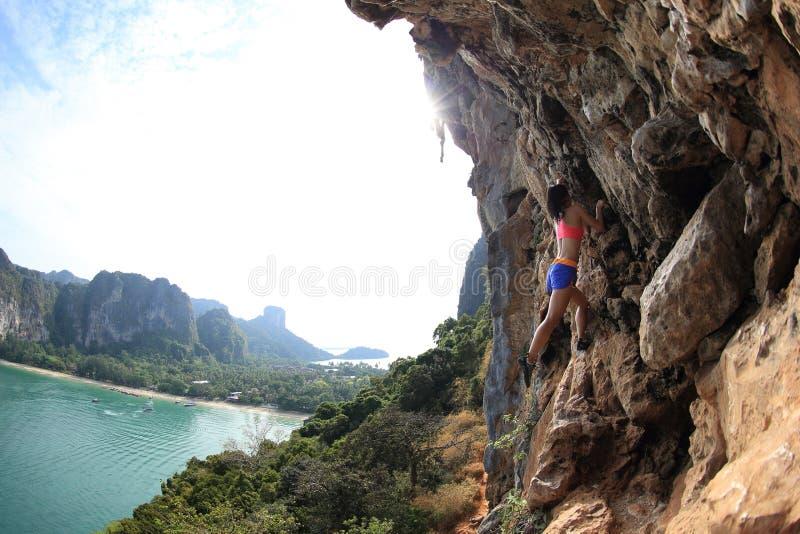 Montanhista de rocha que escala na rocha da montanha do beira-mar imagens de stock royalty free