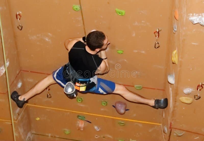 Montanhista de rocha que guarda separações ao escalar a parede marrom imagem de stock