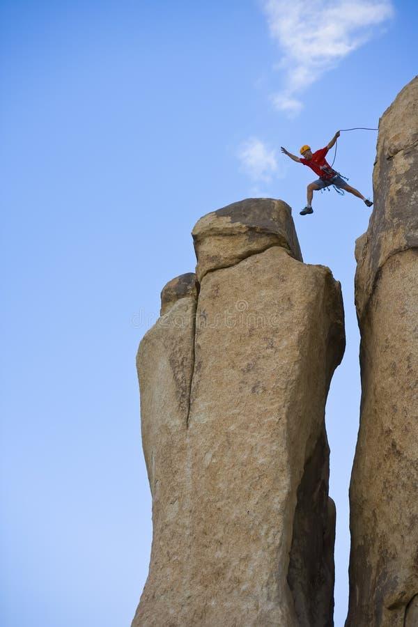 Montanhista de rocha que salta para a cimeira. fotos de stock