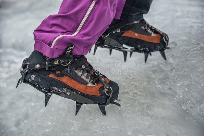 Montanhista em uma cachoeira congelada Close-up dos ganchos de ferro em seu montanhista de gelo dos pés imagem de stock