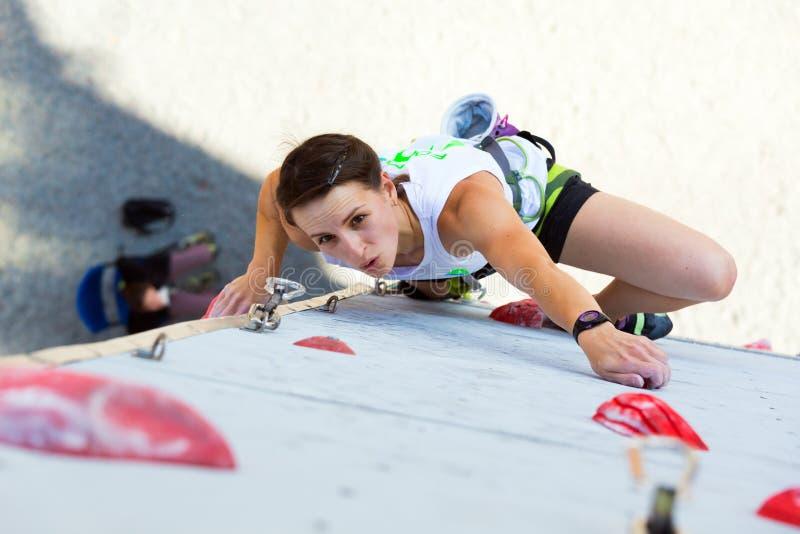 Montanhista fêmea bonito que move na parede de escalada vertical imagem de stock royalty free