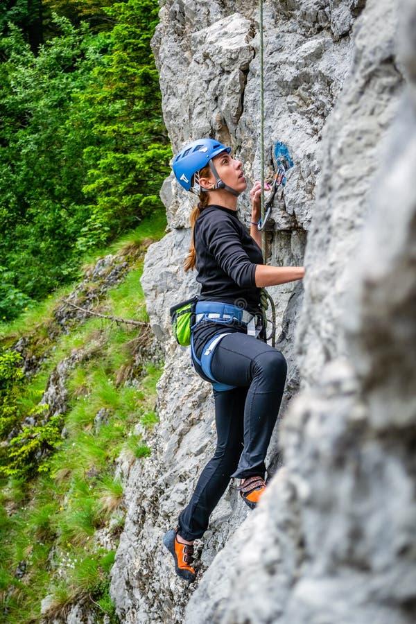 Montanhista fêmea do novato na corda superior, escalando uma rota do esporte perto da cidade de Sinaia, em montanhas de Bucegi, R imagens de stock