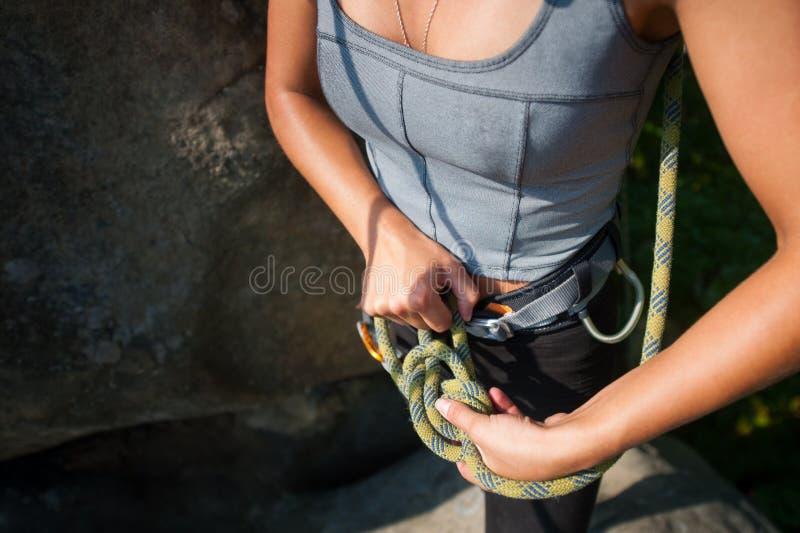 Montanhista fêmea no chicote de fios de segurança que amarra a corda em oito nós fotografia de stock royalty free